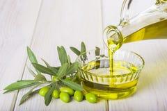 Buteljera hällande jungfrulig extra olivolja i en bunke royaltyfri foto
