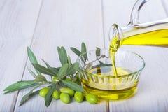 Buteljera hällande jungfrulig extra olivolja i en bunke fotografering för bildbyråer