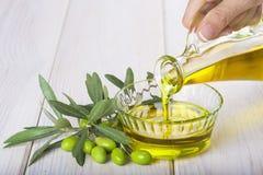 Buteljera hällande jungfrulig extra olivolja i en bunke royaltyfri fotografi