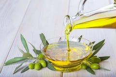 Buteljera hällande jungfrulig extra olivolja i en bunke arkivbild