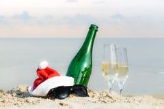 Buteljera och dricka exponeringsglas i sand på havsstranden Arkivbild