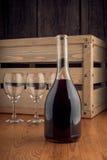 Buteljera och ett exponeringsglas av vin på en träbackgroung Royaltyfri Foto