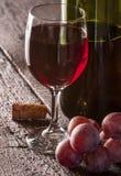 Buteljera och exponeringsglas av rött vin Arkivfoton