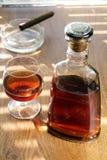 Buteljera och exponeringsglas med cognacen och cigarren Arkivbild