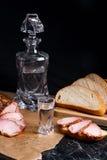 Buteljera och skottexponeringsglas med vodka med skivor av rökt kött på b Arkivbild