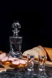 Buteljera och skottexponeringsglas med vodka med skivor av rökt kött på b Arkivbilder
