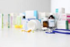 Buteljera preventivpillerar och medicinkapseln på skrivbordet med stetoskopet Royaltyfri Fotografi