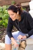 Buteljerar avslappnande spring för den trött kvinnan hörlurarsweatsuit Arkivbild