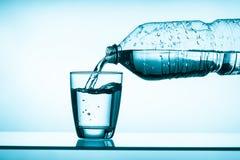 Buteljerat vatten och ett exponeringsglas Royaltyfri Bild