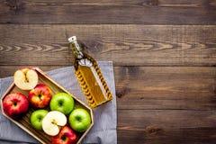 Butelka świeży cydr blisko jesieni jabłek Ciemna drewniana tło odgórnego widoku przestrzeń dla teksta obrazy stock