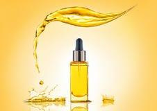 Butelka żółty kosmetyka olej z dużym pluśnięciem above i wiele pluśnięciami wokoło Fotografia Royalty Free