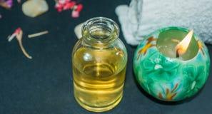 Butelka aromata istotny olej z świeczką, płatek kwitnie Obrazy Royalty Free