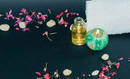 Butelka aromata istotny olej z świeczką, płatek kwitnie Fotografia Royalty Free