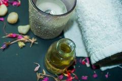 Butelka aromata istotny olej z świeczką, płatek kwitnie Zdjęcie Royalty Free