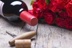 Butelka czerwone wino, corkscrew, prezent, bukiet czerwone róże na nieociosanym starym rocznika tle Fotografia Stock
