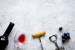 Butelka czerwone wino i corkscrew na kamiennego tła odgórnym widoku mo Zdjęcia Stock