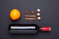 Butelka czerwone wino i pikantność dla rozmyślającego wina na czarnym tle Cynamon, anyżowe gwiazdy, pomarańcze, brown cukier fotografia royalty free