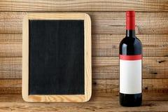 Butelka czerwone wino i pustego miejsca blackboard obrazy stock
