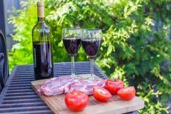 Butelka czerwone wino, stek i pomidory na grillu outdoors, Zdjęcie Royalty Free