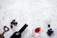 Butelka czerwone wino z winogronami na tekstury tła odgórnym widoku mo Fotografia Stock