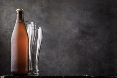 Butelka lekki piwo i dwa pustego szkła na drewnianym stole jako ludzka potrzeba zdjęcie royalty free