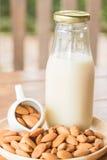 Butelka migdału mleko na drewnianym stole Zdjęcia Royalty Free