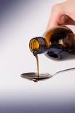 Butelka nalewa ciecz na łyżce Na biały tle Apteka i zdrowy tło Medycyna Kasłanie i zimny lek zdjęcie royalty free