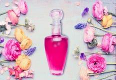 Butelka pachnidło i kwiaty przy podławym modnym tłem, odgórny widok Kwiecisty kosmetyk i piękno fotografia stock