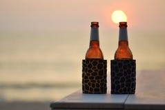 Butelka piwo na plaży przy zmierzchem Obraz Royalty Free