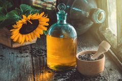 Butelka słonecznikowy olej, drewniany moździerz ziarna i żółty słonecznik na drewnianym stole, Obrazy Stock