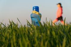 Butelka sport woda butelka stojaki na trawie Sporty styl ?ycia odosobniona straty miara p??postaci ci??aru bia?ej kobiety obrazy stock