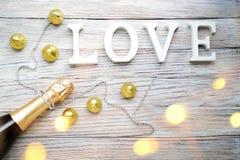 Butelka szampan z czekoladami w złocistym pakunku i sznurek rhinestones na drewnianym tle i słowo miłości obrazy stock