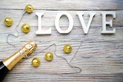 Butelka szampan z czekoladami w złocistym pakunku i sznurek rhinestones na drewnianym tle i słowo miłości obrazy royalty free