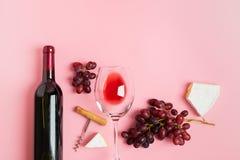 Butelka wino pusty szkło wiązka winogrono plasterki ser na delikatnym różowym tle minimalista Odg?rny widok zdjęcia stock