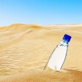 Butelka woda mineralna na piasku Fotografia Royalty Free