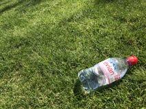 Butelka woda na trawie Obraz Royalty Free