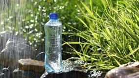 Butelka woda w ogródzie na kamieniach zbliża fontannę zdjęcie wideo
