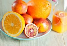 Butelka z świeżym sokiem od pomarańcz i krwionośnych pomarańcz na drewnianej powierzchni Zdjęcie Royalty Free