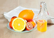 Butelka z świeżym sokiem od pomarańcz i krwionośnych pomarańcz na drewnianej powierzchni Obraz Stock