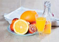 Butelka z świeżym sokiem od pomarańcz i krwionośnych pomarańcz na drewnianej powierzchni Obrazy Royalty Free