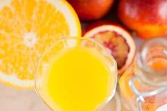 Butelka z świeżym sokiem od pomarańcz i krwionośnych pomarańcz na drewnianej powierzchni Fotografia Stock
