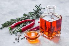 Butelka z chili ziele na kamiennym tle i olejem Zdjęcie Stock
