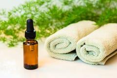 Butelka z istotnym olejem, ręcznikami i zieleniami na łazienka kontuarze, Zdjęcie Stock