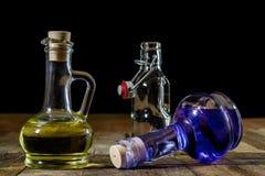 Butelki barwiony ciecz na drewnianym kuchennym stole Drewniany Tabl zdjęcie stock