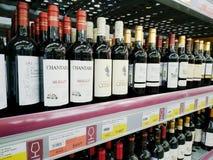 Butelki czerwone wino na półkach sprzedają w supermarkecie Lenta obraz stock