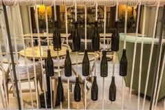 Butelki dołączali arkany przed stołami w kawiarni Fotografia Stock