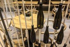 Butelki na arkanach i stoły w kawiarni Fotografia Royalty Free