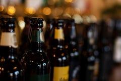 Butelki piwo stojak w tle plama pub w wieczór obrazy stock