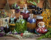 Butelki tincture, napój miłosny, olej, zdrowe jagody i ziele, zdjęcie royalty free