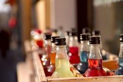 Butelki w drewnianym pude?ku wype?niaj?cym z barwionymi napojami zdjęcie stock